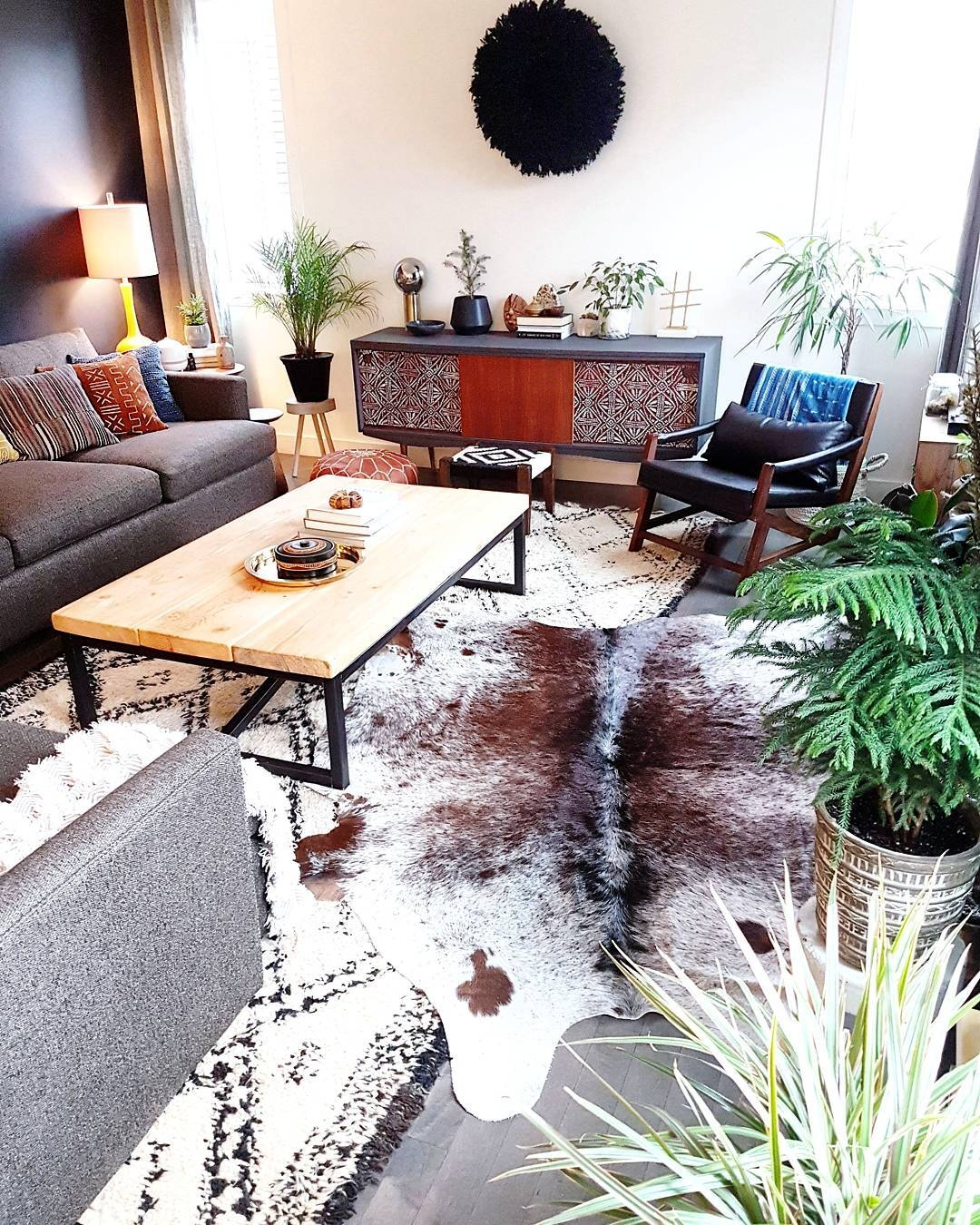 A cowhide rug grey white black is just as class as the home features, from wooden floor to fireplace decor and windows gives this a modern feel.